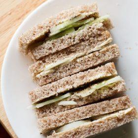 Gros plan de sandwichs au concombre empilés avec les couches visibles de concombre et de pain placé sur une plaque blanche