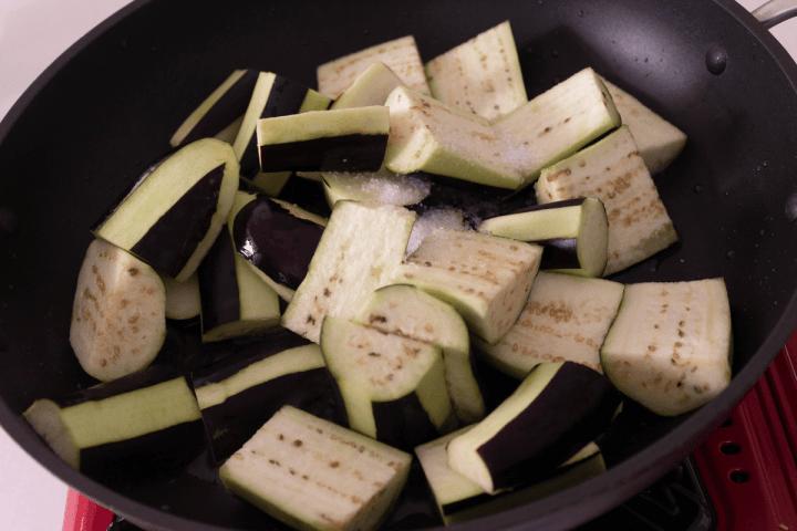 Morceaux d'aubergine avec du sel dans un wok.