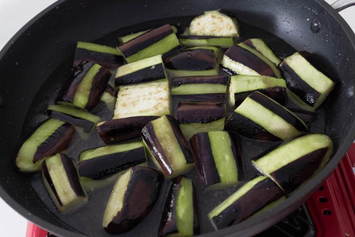 Morceaux d'aubergine dans l'eau dans un wok.