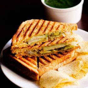 sandwich grillé avec le côté de remplissage montré quelques gaufrettes de pommes de terre sur une plaque blanche