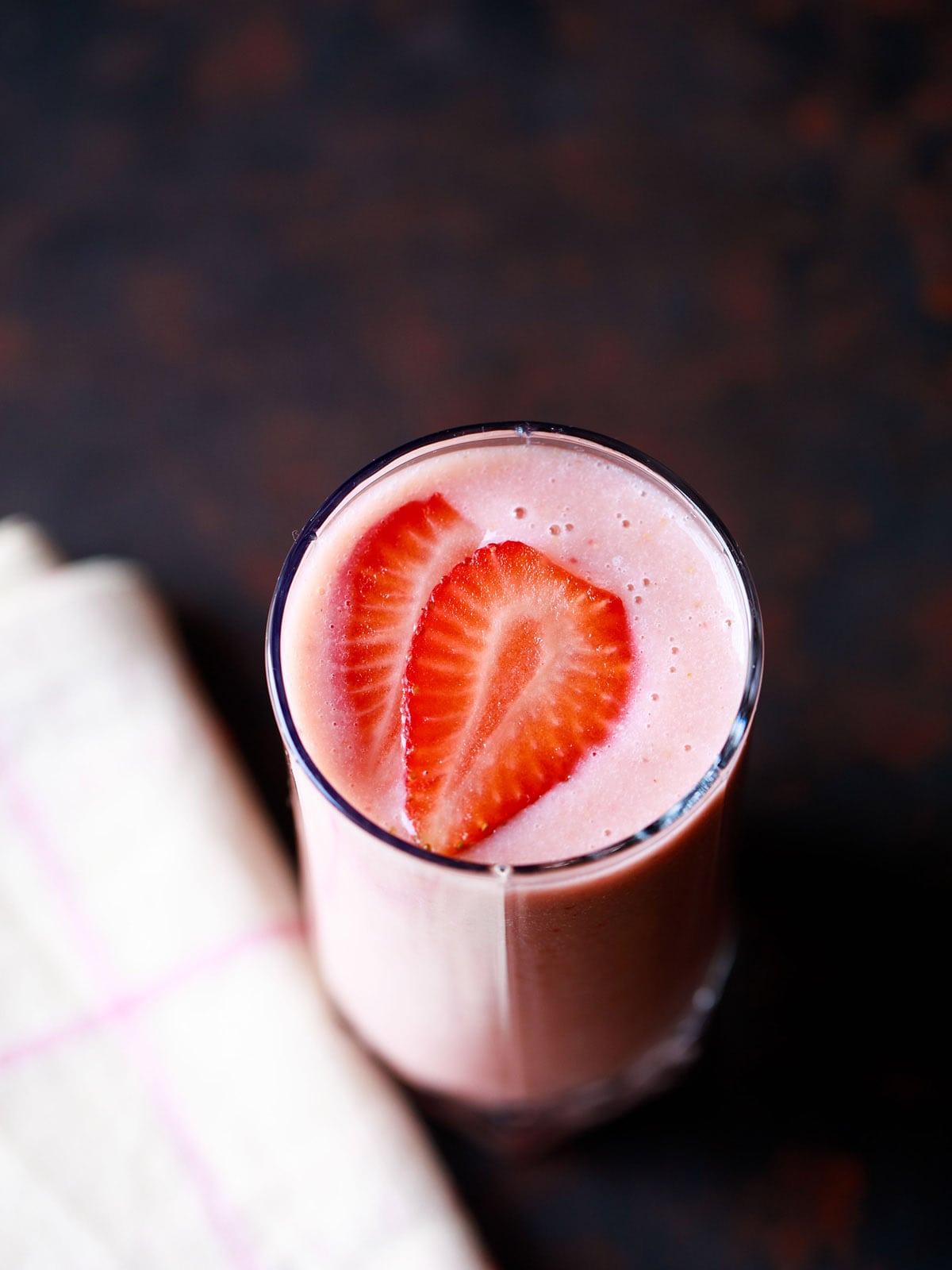 Smoothie aux fraises dans un verre garni de tranches de fraises avec une serviette crème sur une planche brun noir foncé