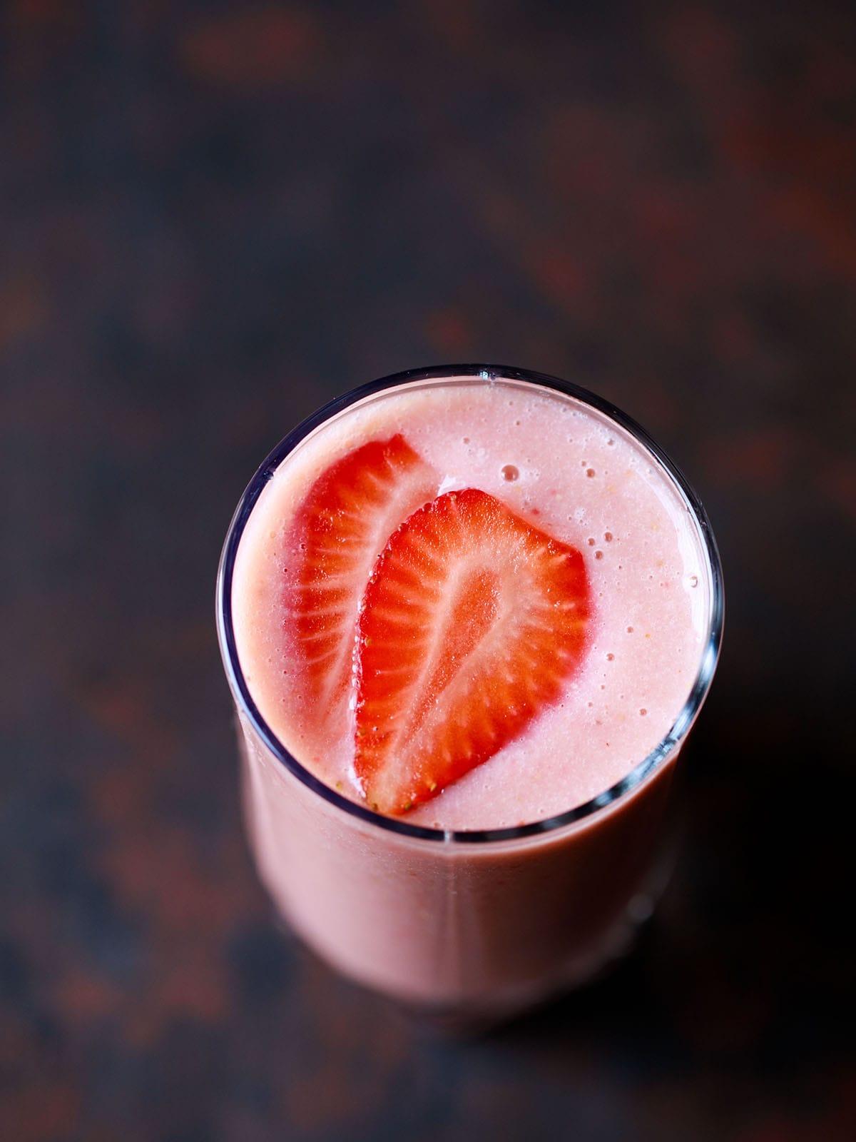 Smoothie fraise et banane dans un verre garni de tranches de fraise sur une planche brun noir foncé