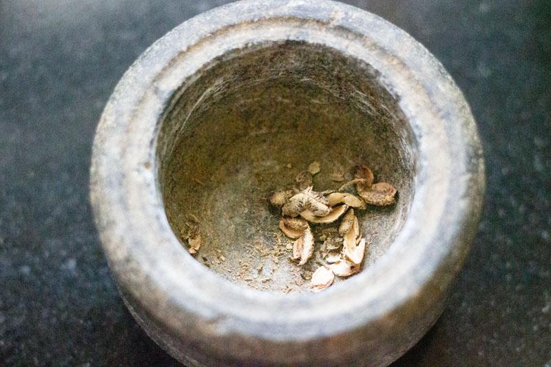 broyage du poivre de sichuan dans un mortier de pierre
