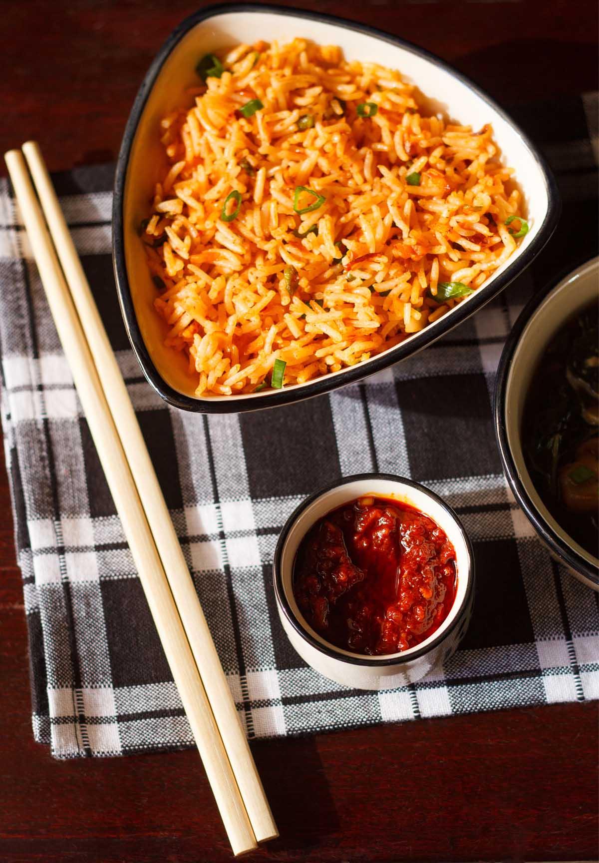 Coup de frais généraux de sauce schezwan dans un petit bol avec des baguettes et du riz frit schezwan sur une serviette à carreaux noir et blanc