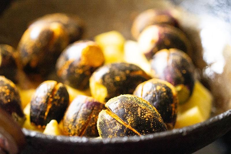 brinjals farcis ajoutés aux pommes de terre dans un wok