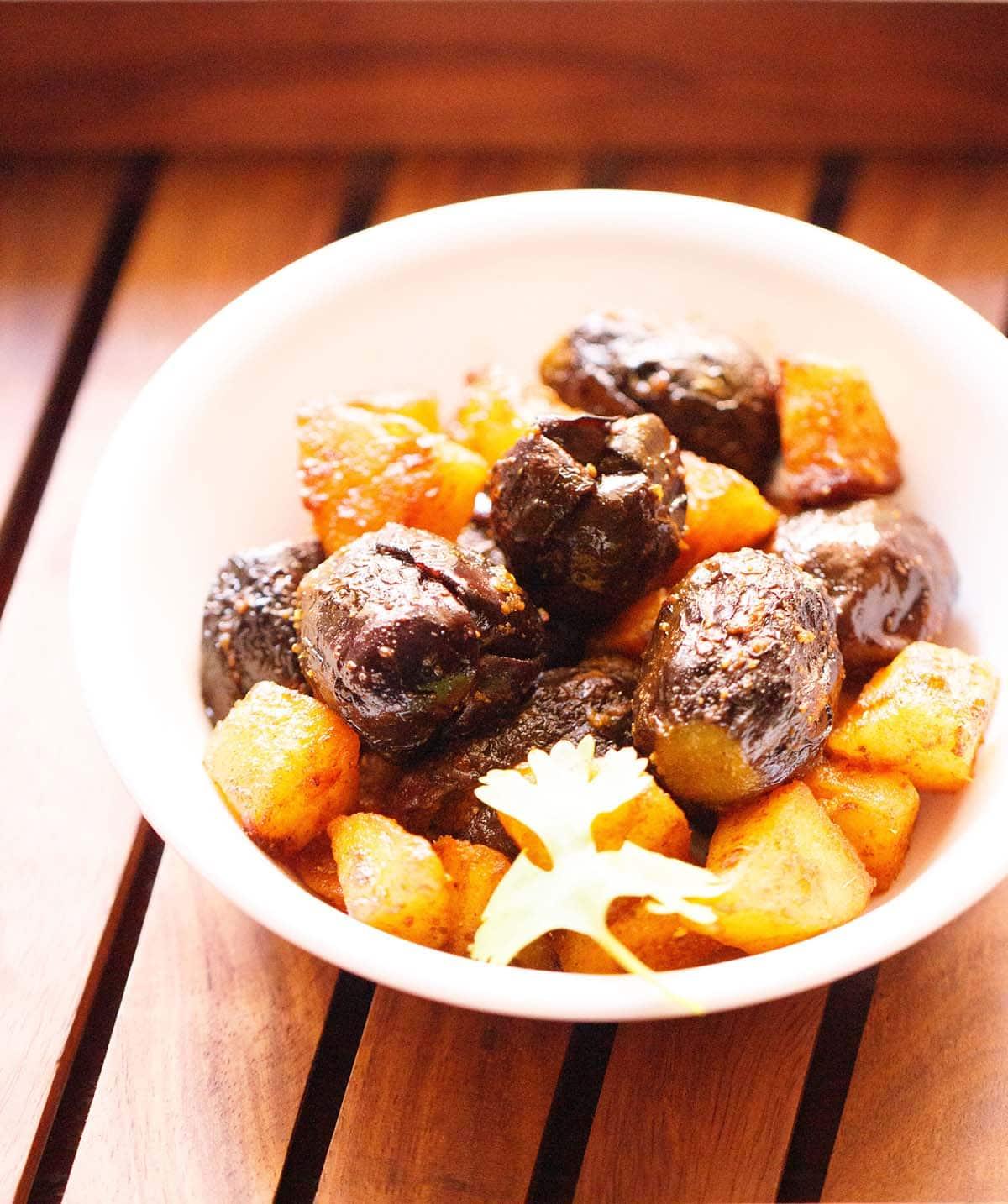 bharwa baingan avec pommes de terre dans un bol blanc avec un brin de coriandre sur un plateau en bois