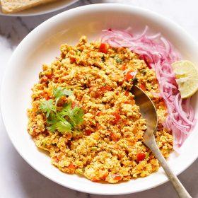 Paneer Bhurji servi dans un bol blanc peu profond garni d'un brin de coriandre avec une cuillère à l'intérieur du bhurji et garni d'oignons tranchés et d'un quartier de citron