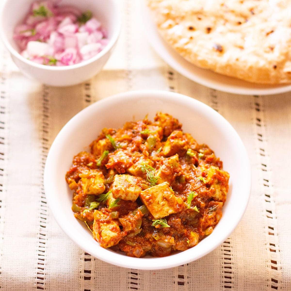 paneer tawa masala avec des feuilles de coriandre garnir dans un bol blanc sur un linge crème avec une assiette latérale de roti et un petit bol latéral d'oignons rouges hachés et de coriandre