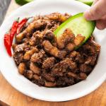 Thịt Kho Mắm Ruốc dans un bol avec une main plongeant le concombre dedans.