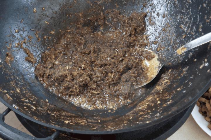 Pâte de citronnelle et crevettes dans un wok.