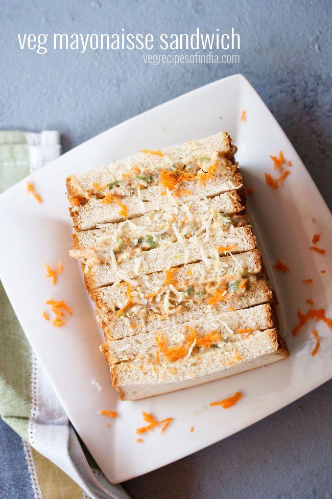 sandwich à la mayonnaise aux légumes garni de carottes râpées et de fromage sur une plaque carrée blanche