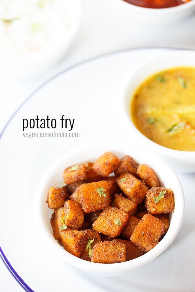 frites de pommes de terre servies dans un bol placé sur une assiette blanche avec curry de lentilles dans un autre bol
