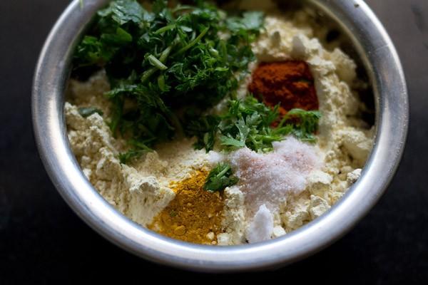dans un bol, ajouter la farine de pois chiches, les feuilles de coriandre et les épices