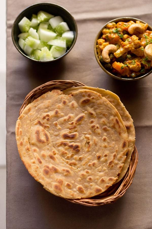 Lachha Paratha servi dans un panier en canne avec sauce et salade