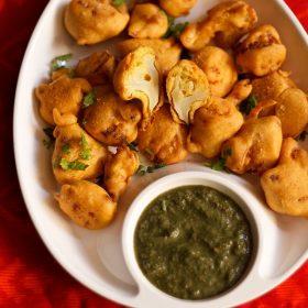 gobi pakora servi dans une assiette blanche avec chutney vert