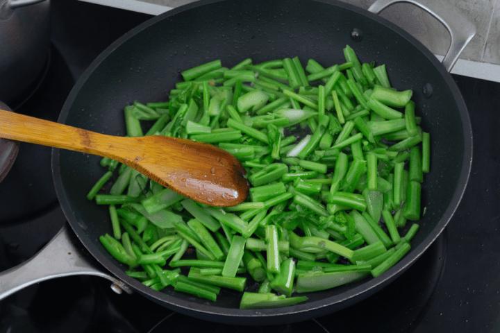 Segments de tige de brocoli chinois dans un wok avec une cuillère en bois.