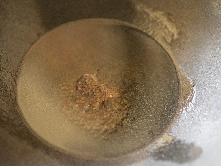 ajouter les graines de moutarde à l'huile dans un kadai