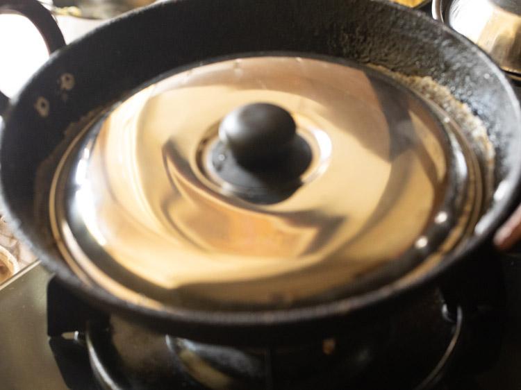 couvrir le kadai avec le couvercle et cuire les cubes de pomme