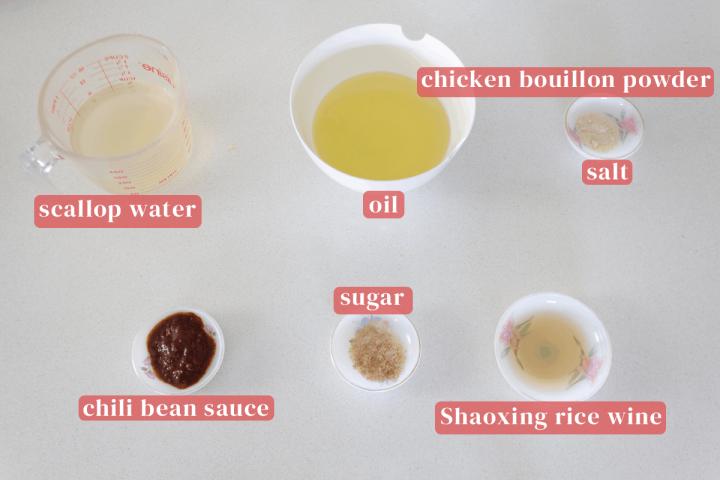 L'eau des pétoncles dans une tasse à mesurer avec un bol d'huile et des plats de poudre de bouillon de poulet, sel, sucre, vin de riz Shaoxing et sauce aux haricots chili.