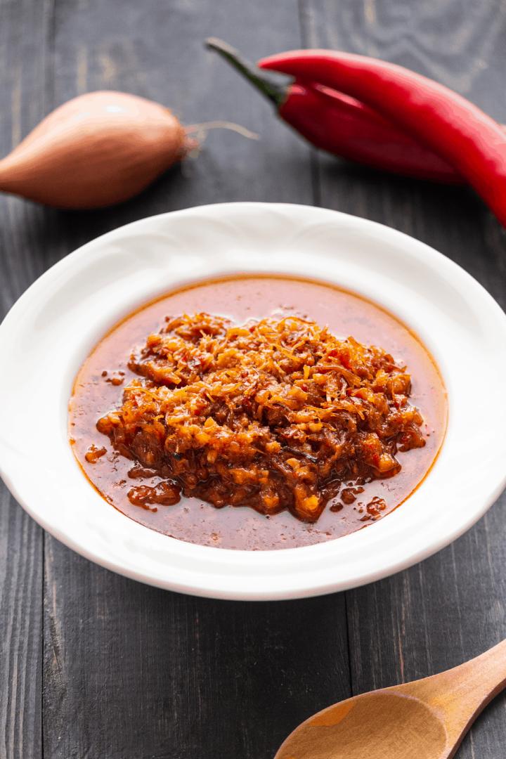 Sauce XO cuite dans une casserole avec une cuillère en soulevant un peu.