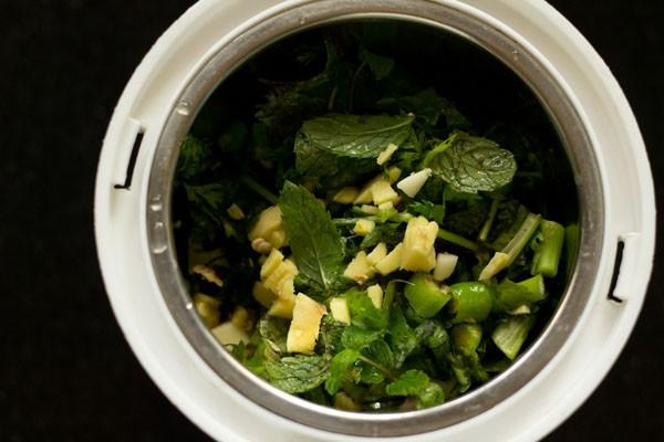 dans un bol de broyeur ajouter le gingembre ail les feuilles de menthe les feuilles de coriandre et le piment vert