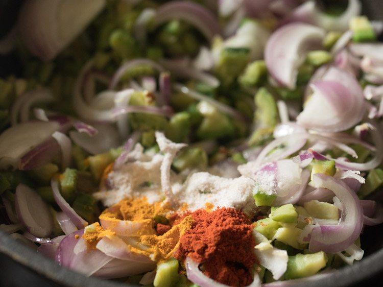 ajouter des épices au mélange d'oignons karela