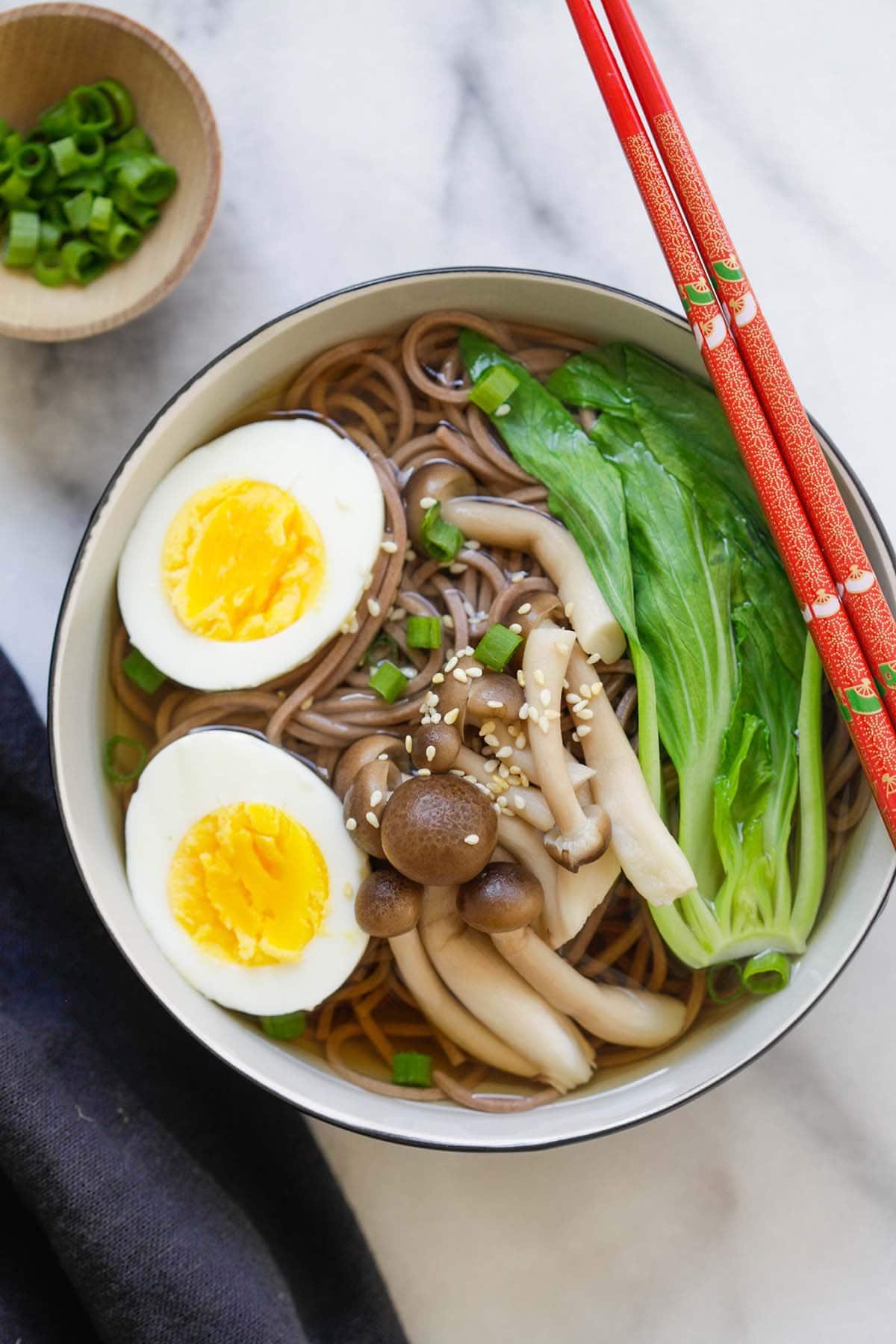 Soupe de nouilles soba japonaise rapide et facile avec des œufs durs et des légumes verts asiatiques dans un bol.
