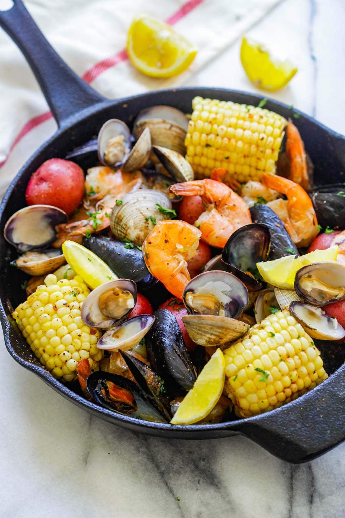 Clambake facile (bouillir les palourdes) dans une poêle avec des palourdes, des moules, des crevettes, du maïs et des pommes de terre.