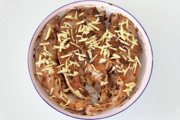 Poisson cuit à la vapeur non cuit avec sauce aux haricots noirs dans un plat.