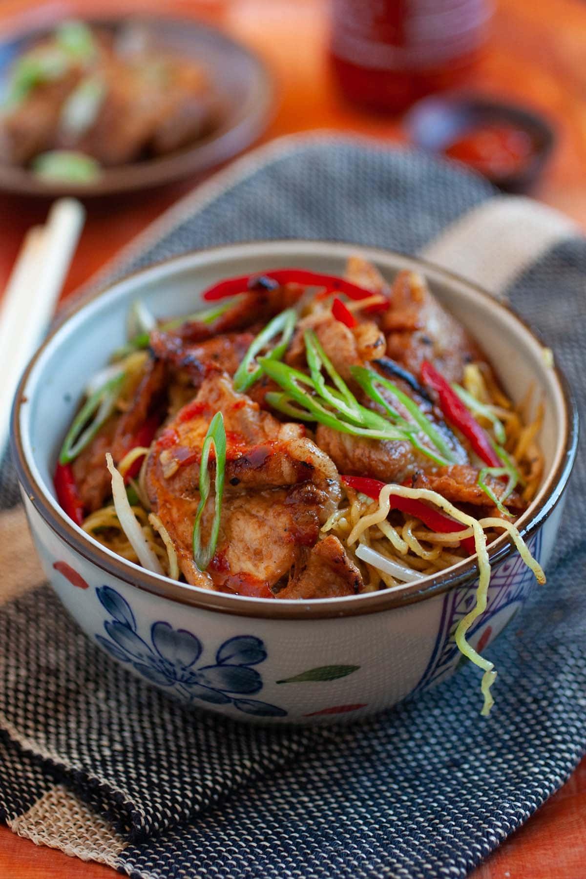 Du porc aigre-doux authentique et facile sur des nouilles sautées servies dans un bol.