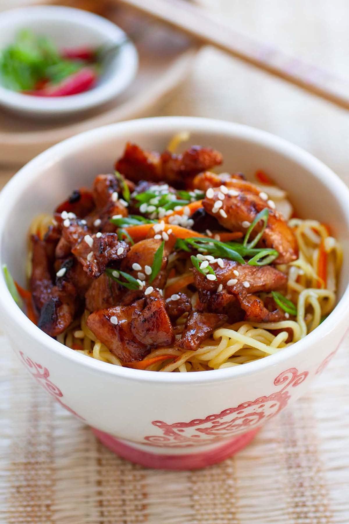 Nouilles sautées au poulet avec carottes et oignons verts dans un bol.