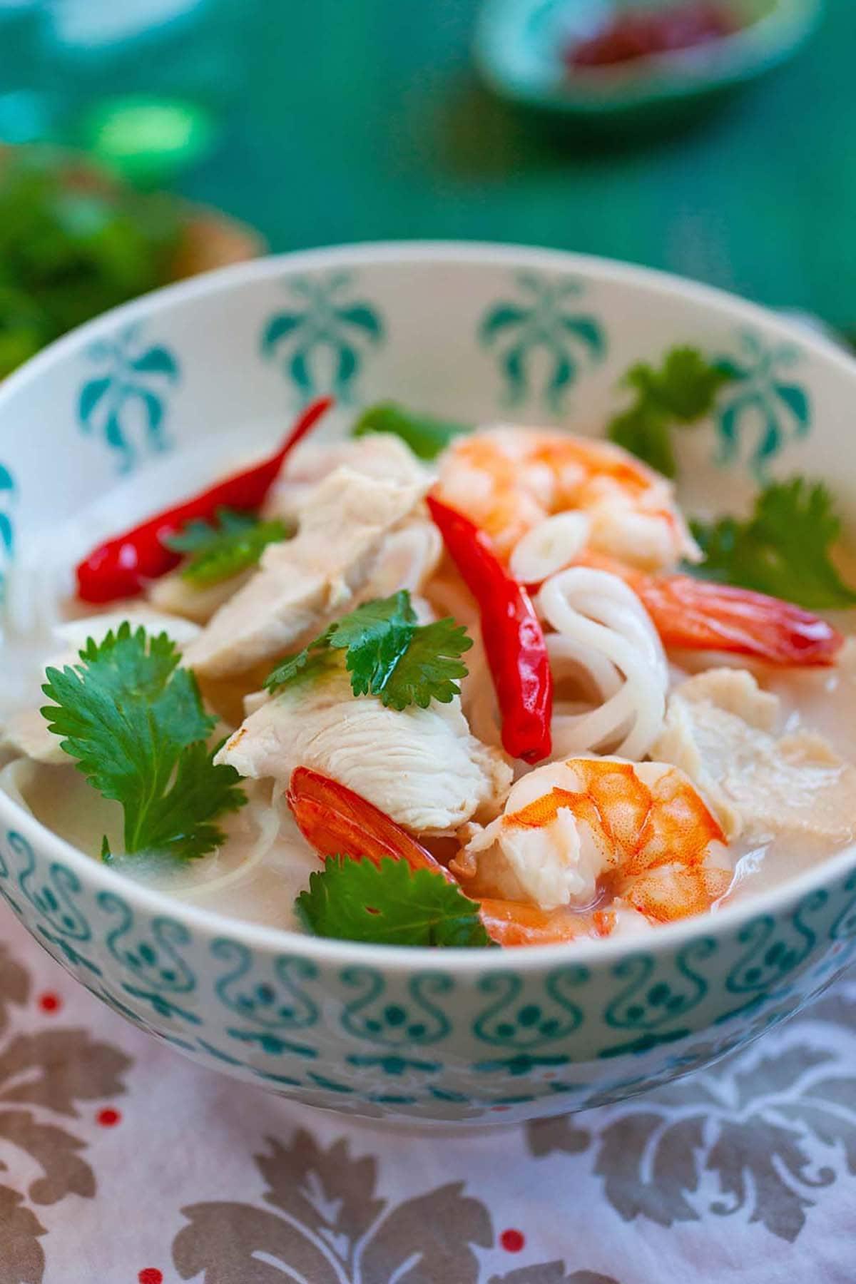 Soupe de nouilles thaïlandaise maison riche et savoureuse à la noix de coco et aux crevettes prêtes à servir.