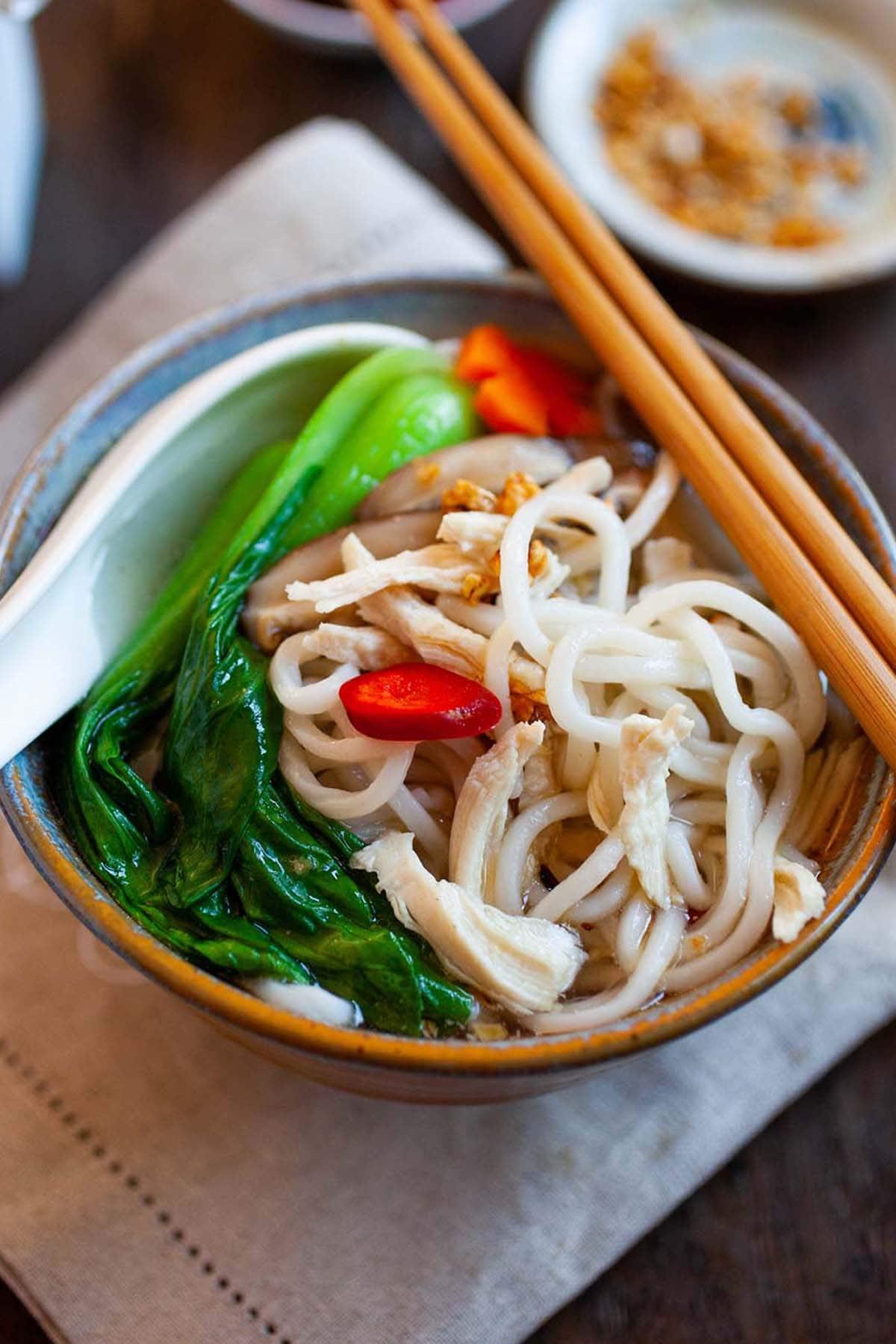 Soupe chinoise au poulet et aux nouilles avec bouillon de poulet, nouilles et bok choy dans un bol.