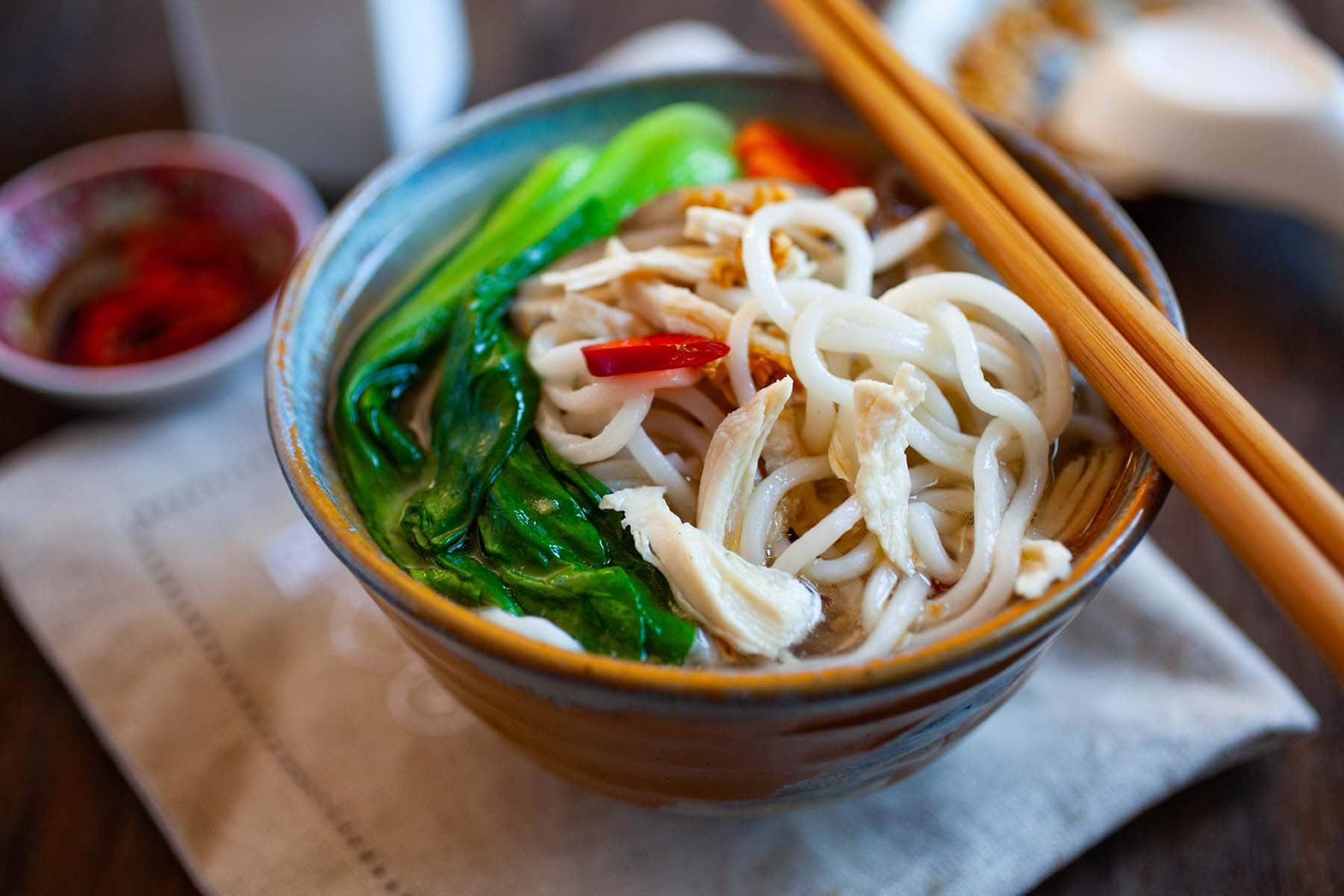 Soupe de nouilles chinoises au poulet, bok choy et nouilles dans un bol blanc.