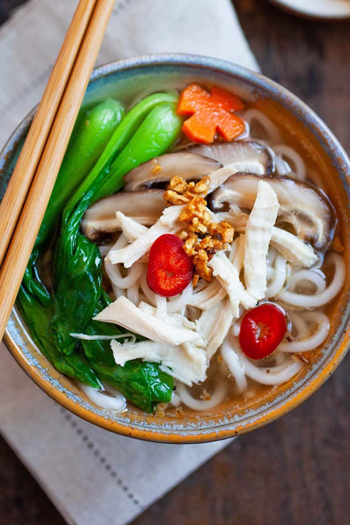 Soupe de nouilles asiatique au poulet, légumes bok choy et nouilles dans un bol.