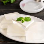 Thạch Dừa morceaux sur une assiette avec de la menthe sur le dessus.