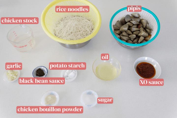 Bouillon de poulet dans une tasse à mesurer avec des passoires de nouilles et pipis et des plats de sauce XO, huile, fécule de pomme de terre, sucre, sauce aux haricots noirs, poudre de bouillon de poulet et ail haché.