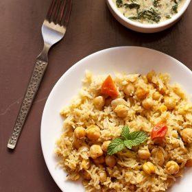 chana pulao servi dans une assiette blanche avec raïta aux épinards