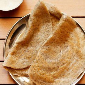 dal dosa mélangé servi dans une assiette avec un côté de chutney de noix de coco