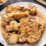 Poisson cuit à la vapeur avec sauce aux haricots noirs sur une assiette.
