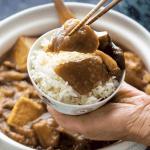 Aubergine braisée au tofu dans un pot d'argile derrière une main tenant un bol de riz avec des morceaux d'aubergine sur elle soutenue par des baguettes.