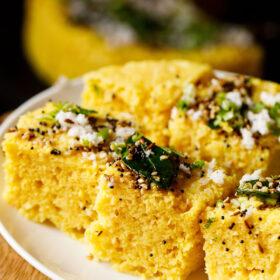 Prise de vue à 45 degrés de carrés de khaman dhokla sur une assiette blanche garnie de coriandre, de feuilles de curry et du mélange de feuilles de curry frit et d'épices