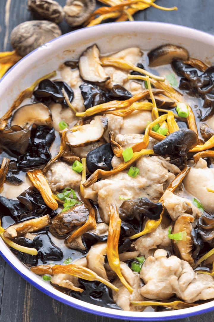 Gros plan du poulet cuit à la vapeur avec des champignons et des fleurs de lys séchées dans un plat.