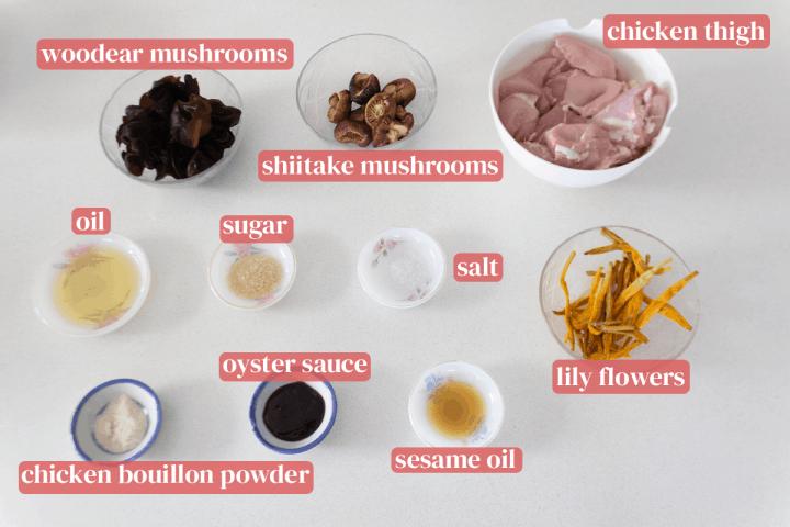 Bols de champignons woodear et shiitake, cuisses de poulet et fleurs de lys avec des plats d'huile de sésame, sel, sucre, sauce aux huîtres, poudre de bouillon de poulet, sucre et huile.