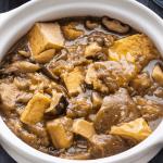 Aubergines braisées au tofu dans un pot en terre cuite.