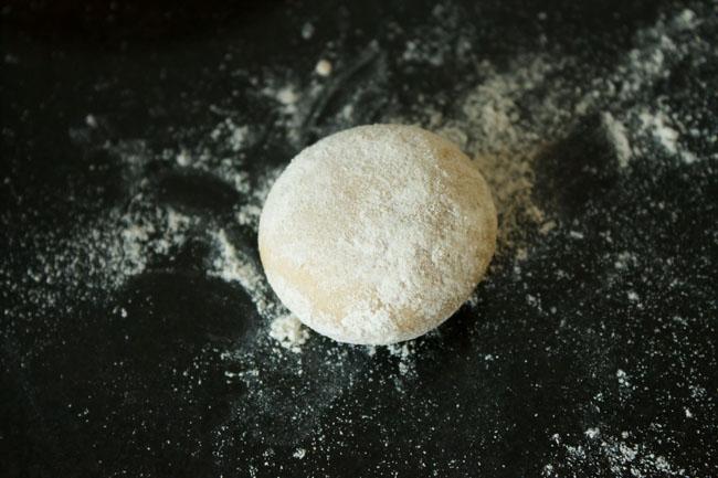 rond de pâte aplati saupoudré de farine sur une surface saupoudrée de farine