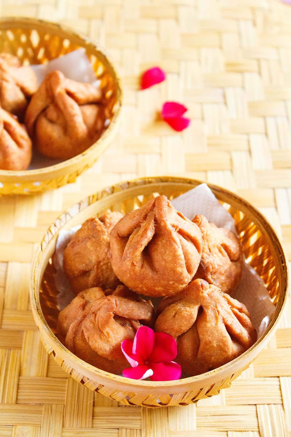 modak frit dans un bol rond en bambou avec une fleur rose foncé placée sur une natte de bambou
