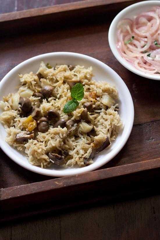 pulao aux champignons servi sur une assiette blanche avec un côté d'oignons tranchés sur une petite assiette blanche