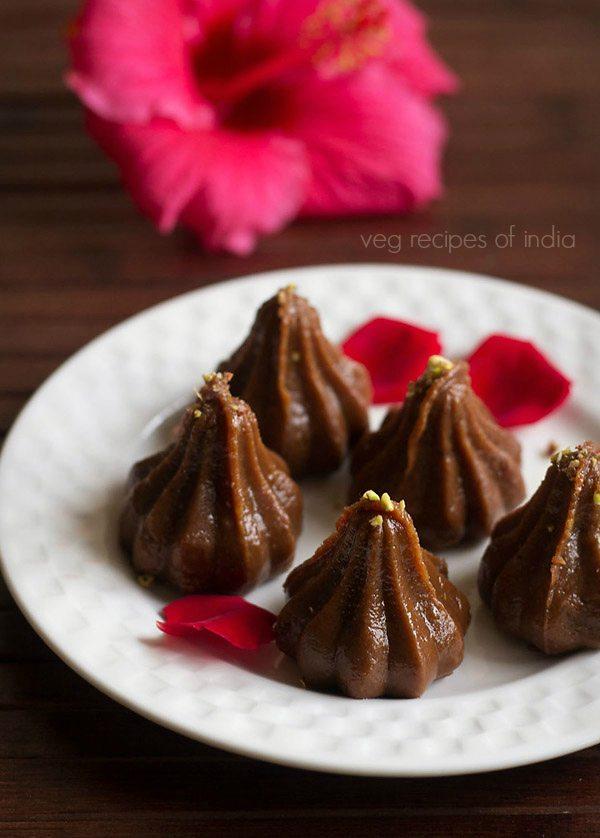 modak au chocolat sur un plateau blanc garni de pétales de rose
