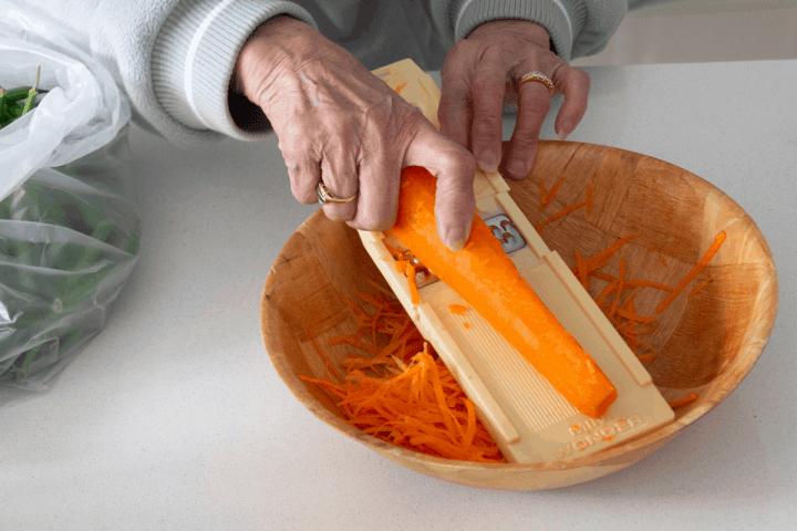 Une main coupant une carotte dans un bol à l'aide d'une mandoline.